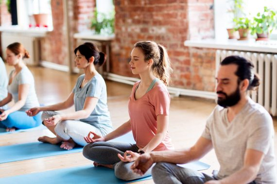 group of students seated on yoga mats in a meditation pose
